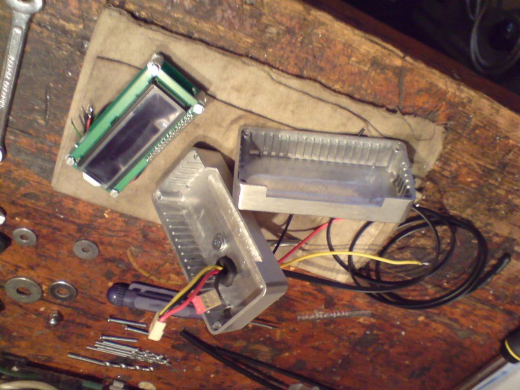 Sam moduł również wymagał małej przebudowy. Żeby maksymalnie zmniejszyć jego płytkę drukowaną i móc wyśrodkować wyświetlacz względem obudowy usunąłem przyciski sterowania (odciąłem niepotrzebną część płytki). Zamiast zastosowanych początkowo mikrostyków wlutowałem przewody. Zasada działania jest prosta, masa i trzy włączniki - tryb ustawienia, zwiększ lub zmniejsz parametr (te ostatnie dwa odpowiadają również za sterowanie jasnością wyświetlacza). W obudowie oprócz wycięcia okienka musiałem spiłować żebra od strony okienka, żeby dobrze dopasować szybkę. Na zdjęciu widać też otwór z przelotką na przewody (masa, plus, plus podtrzymujący zegarek) oraz do czujnika temperatury. W dolnej części dałem długą śrubę M5, która będzie mocować moduł do obudowy zegarów. Do skręcenia całości wykorzystałem oryginalne, nagwintowane fabrycznie, otwory w narożnikach jednej z obudów, a w drugiej rozwierciłem je na przelot pod śruby z płaskimi łebkami.