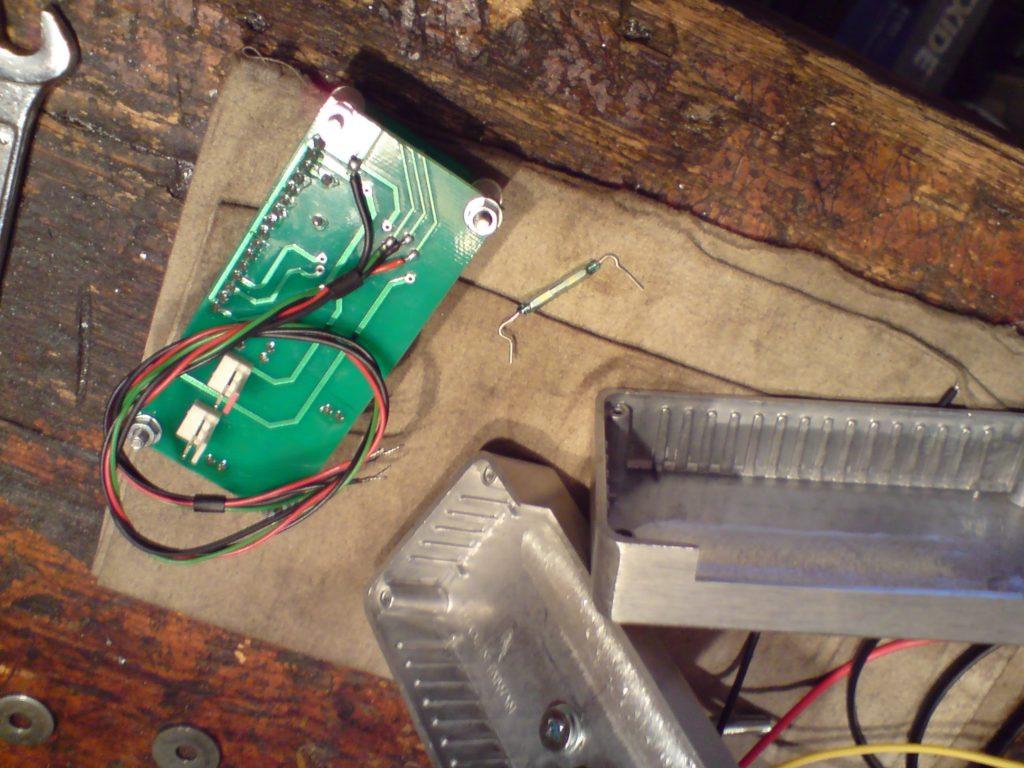 Tył modułu po przeróbkach. Widać przewody, które przylutowałem do ścieżek od odciętych wyłączników (mikrostyków). Obok modułu, na szmatce, widać kontaktron, który zastąpi mikrostyk. Tył modułu został pozbawiony ochronnej płytki - nie będzie potrzebna. Jak widać całość znacznie się zmniejszyła. Dzięki temu bez trudu zmieści się w obudowie.