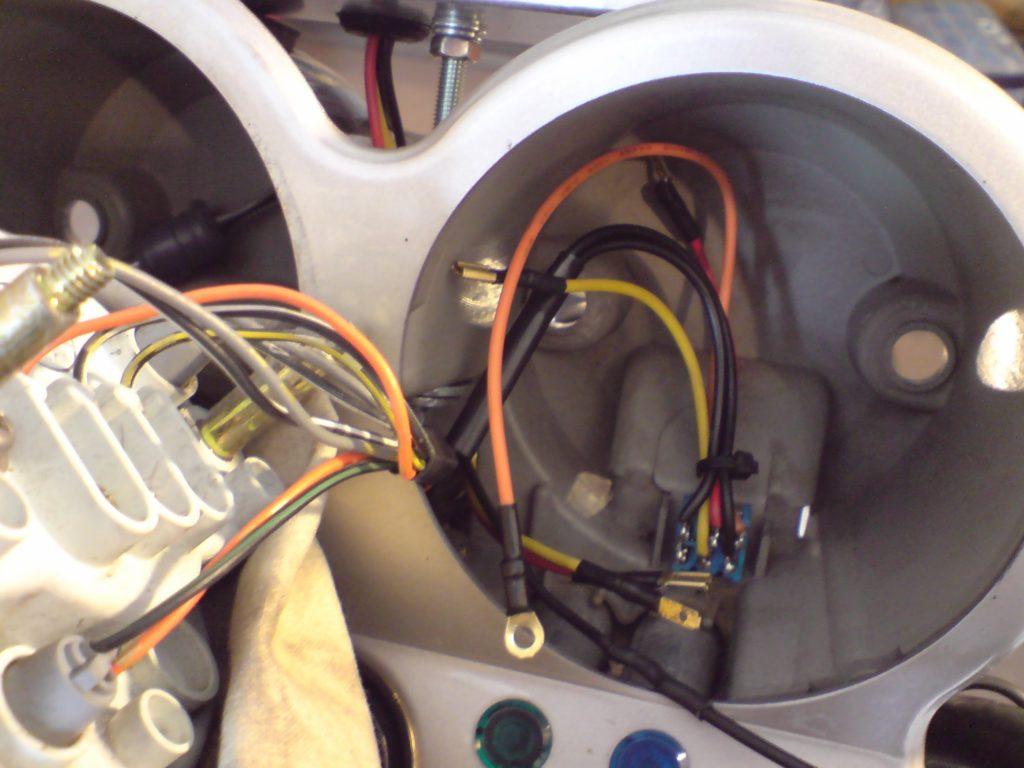 Nie mam za dużo zdjęć z tej fazy montażu, bo wszystko robiłem na biegu. Centralna śruba 5 mm wchodzi w otwór wywiercony w plastiku zegarów. Do tego podkładki zwykłe i sprężyste oraz kontra. Na środku w głębi zegarów, w łączeniu kubków, widać dużą podkładkę. Ma rozłożyć siły na większą powierzchnie. Pod obudową modułu dałem małe, gumowe odboje (nie widać na zdjęciu), żeby nie rysować kubków. Montaż jest mało inwazyjny i b. szybko można wrócić do seryjnego wyglądu (np. moduł idzie do nowego motocykla itp.). Na razie wszystko się trzyma.
